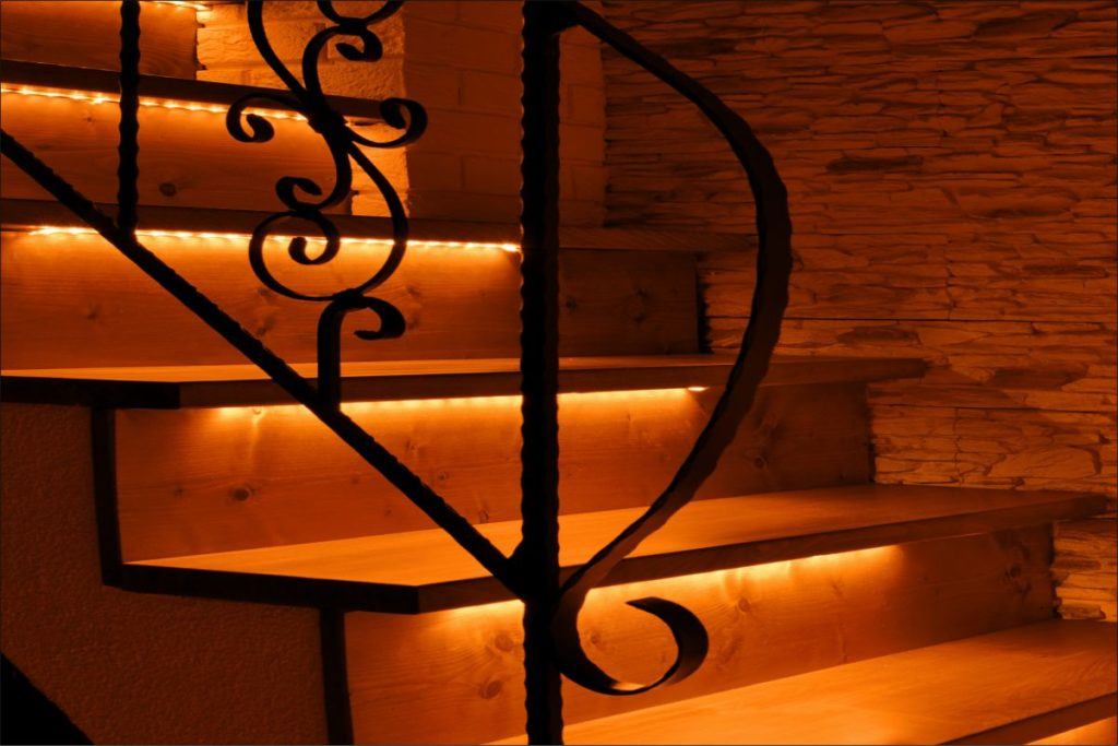 Orange LED lighting wooden stairs illuminated with LED strips. Effective LED lighting of smart stairs.