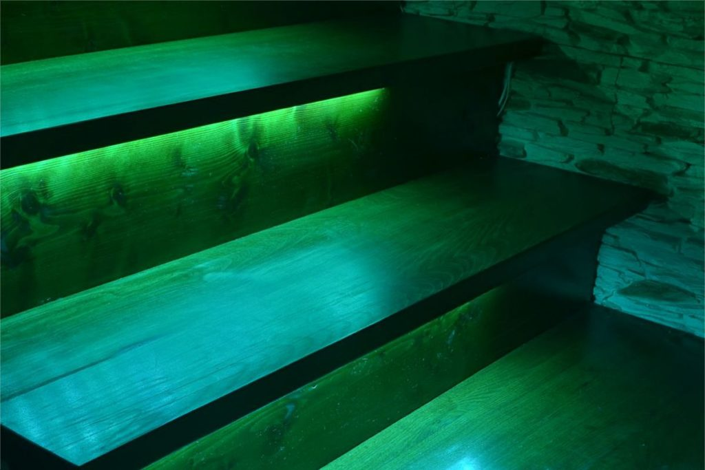 Backlight stairs with LED strip in green color
