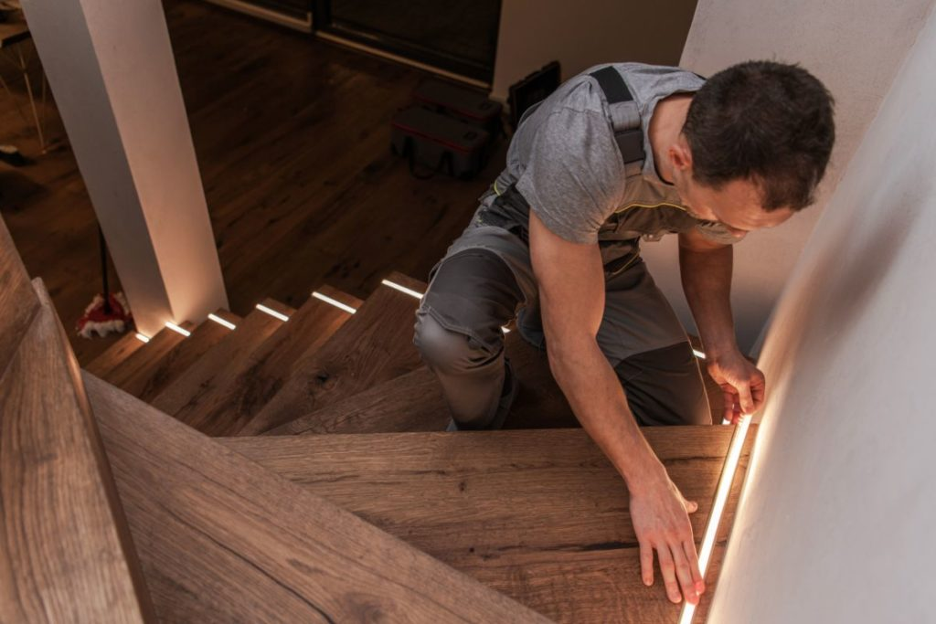 Worker installing home stairs modern illumination